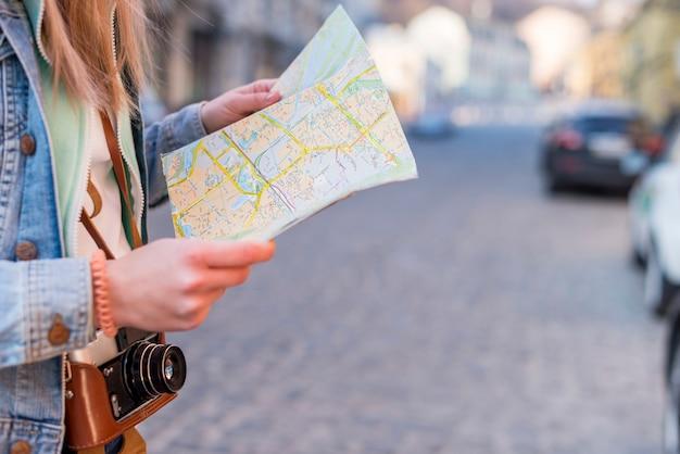Weiblicher reisender, der richtung auf standortkarte im stadtzentrum sucht