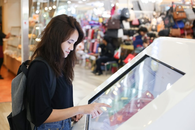 Weiblicher reisender, der wechselwirkende informationen der digitalen medien im einkaufszentrum verwendet