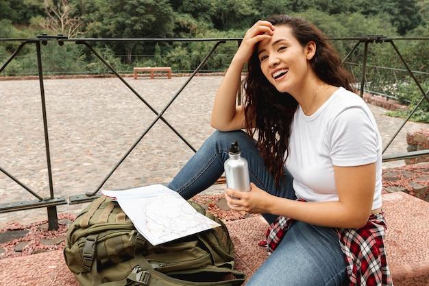 Weiblicher reisender halt des smiley, zum zu hydratisieren