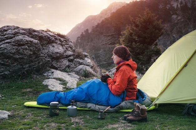 Weiblicher reisender in einem schlafsack nahe dem zelt in den bergen, türkei