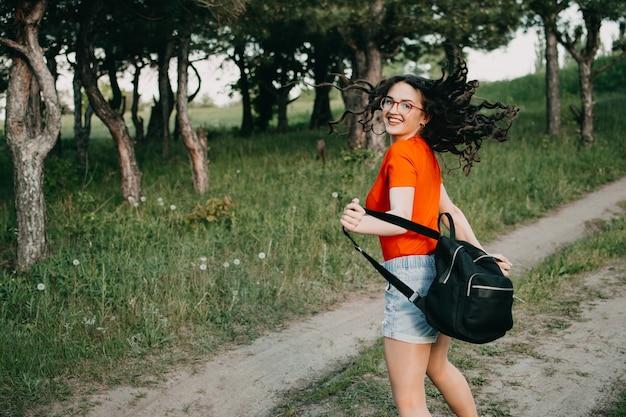 Weiblicher reisender junger mädchen-tourist, der auf landstraße geht.