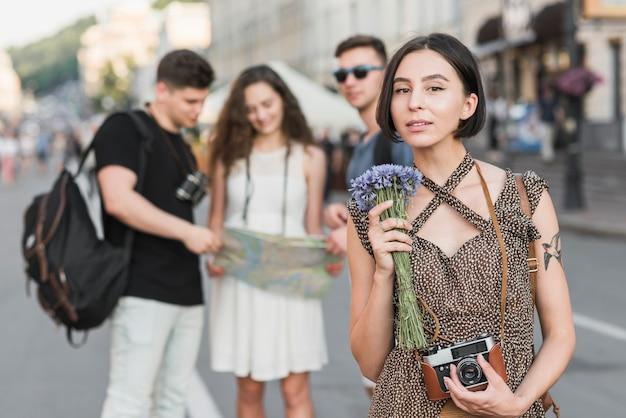 Weiblicher reisender mit blumen und kamera