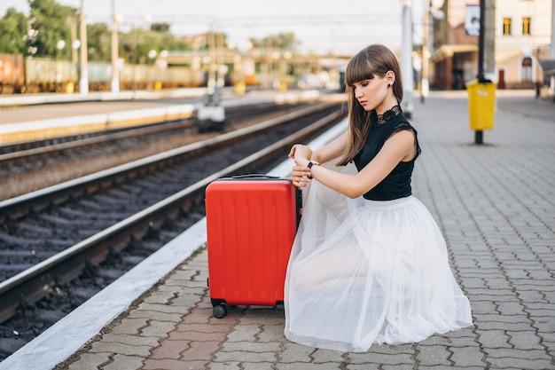 Weiblicher reisender mit rotem koffer, der zug am bahnhof wartet