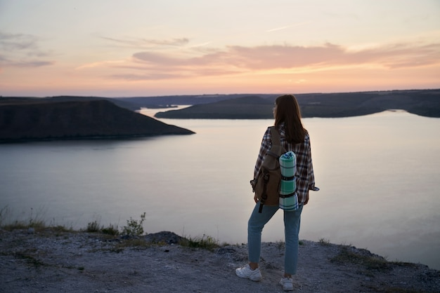 Weiblicher reisender mit rucksack, der auf einem hügel in der bucht von bakota steht?