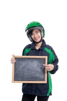 Weiblicher reiter, der helm hält, der leere tafel lokalisiert über weißem hintergrund hält