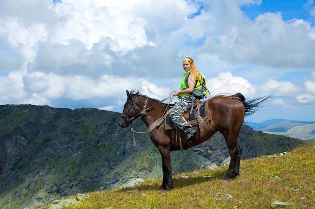 Weiblicher reiter zu pferd in den bergen