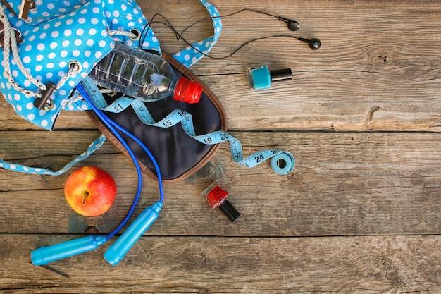 Weiblicher rucksack mit sportausrüstung, kosmetik, maßband, wasser. ansicht von oben