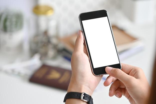 Weiblicher rührender smartphone des leeren bildschirms der nahaufnahme auf tabelle.