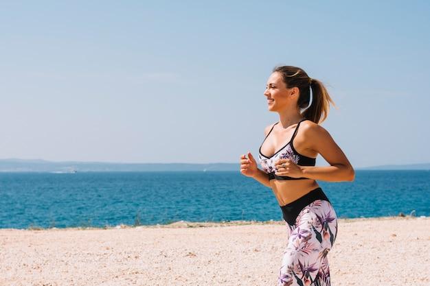 Weiblicher rüttler, der nahe dem meer am strand läuft