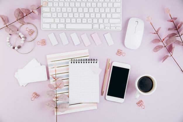 Weiblicher schreibtischarbeitsplatz mit tastatur, smartphone, goldene klipps auf veilchen