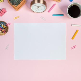 Weiblicher schreibtischarbeitsplatz mit weißbuchmodell auf rosa hintergrund.