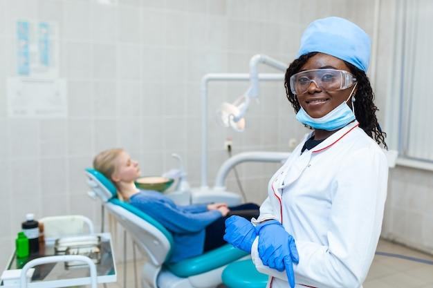 Weiblicher schwarzer zahnarzt in zahnarztpraxis, der mit patientin spricht und sich auf die behandlung vorbereitet. moderne medizinische geräte