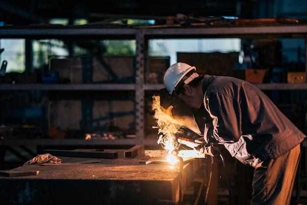 Weiblicher schweißer, der in der schwerindustriefabrik arbeitet.