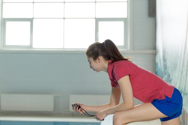 Weiblicher schwimmtrainer, der stoppuhr in der nähe des pools betrachtet.