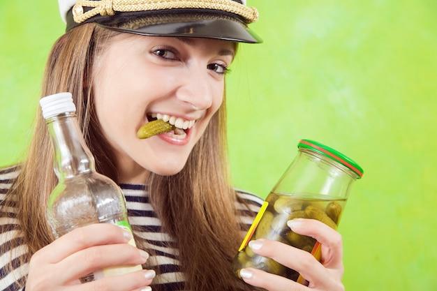 Weiblicher seemann mit flasche wodka und gurke