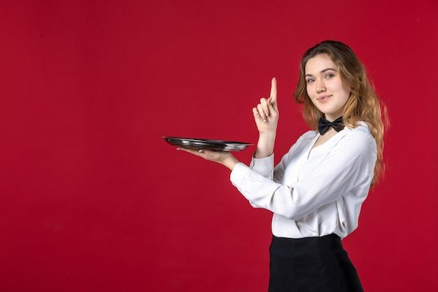 Weiblicher server-schmetterling am hals und hält tablett nach oben auf rotem hintergrund