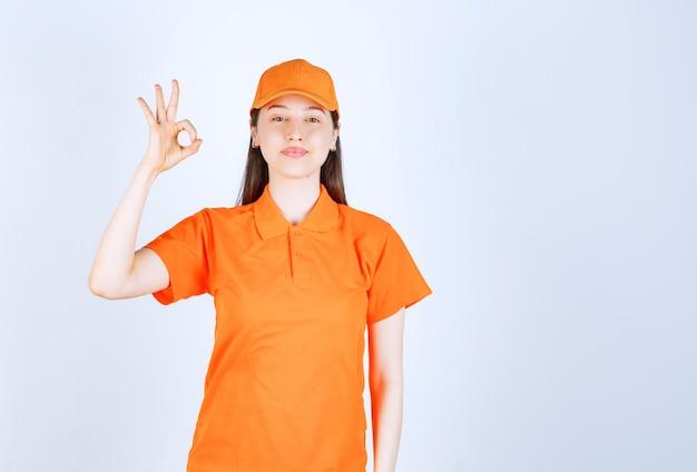 Weiblicher servicemitarbeiter, der orangefarbene uniform trägt und positives handzeichen zeigt.