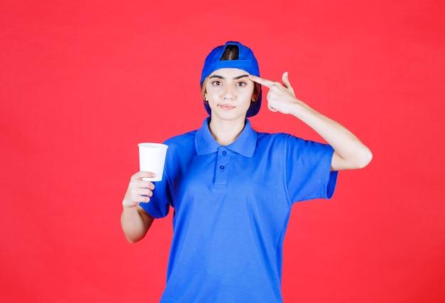 Weiblicher servicemitarbeiter in blauer uniform, der eine einweg-tasse getränk hält und eine gute idee hat.