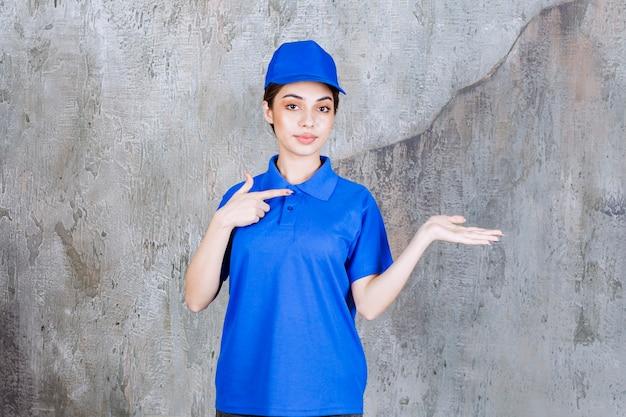 Weiblicher servicemitarbeiter in blauer uniform mit der rechten seite.
