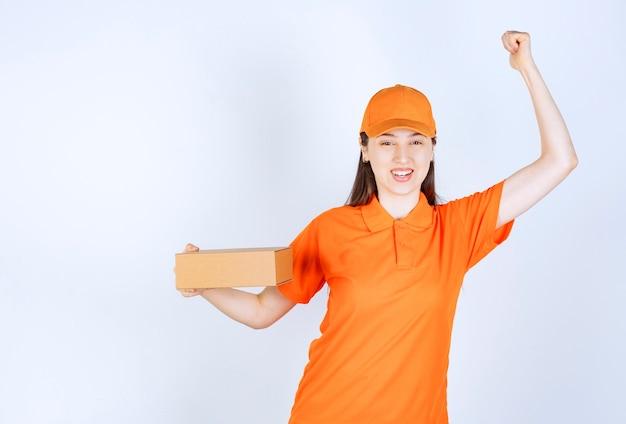 Weiblicher servicemitarbeiter in der orangefarbenen uniform, die einen karton hält und erfolgreiches handzeichen zeigt.
