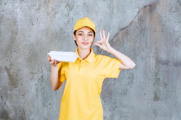 Weiblicher servicemitarbeiter in gelber uniform, die eine plastikbox zum mitnehmen hält und positives handzeichen zeigt.
