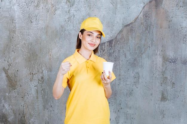 Weiblicher servicemitarbeiter in gelber uniform, die einen plastikbecher hält und positives handzeichen zeigt.