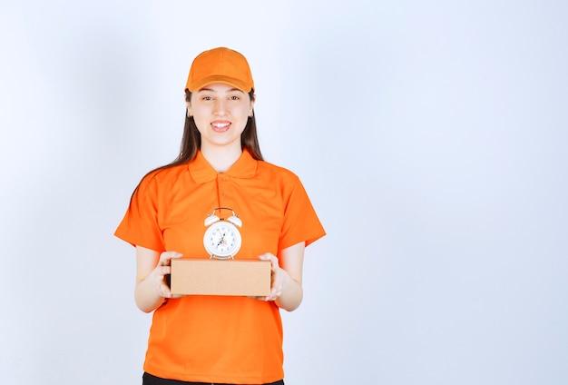 Weiblicher servicemitarbeiter in orangefarbener uniform, die einen karton und einen wecker hält.