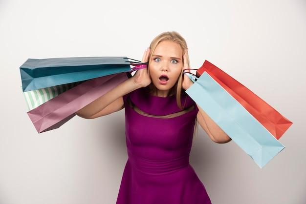 Weiblicher shopaholic mit bunten einkaufstüten, die ihre ohren bedecken. hochwertiges foto