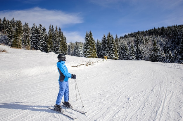 Weiblicher skifahrer auf einer skisteigung am skiort