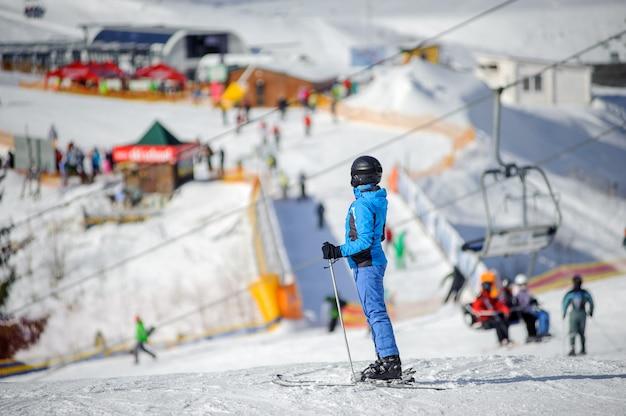 Weiblicher skifahrer auf einer skisteigung an einem sonnigen tag