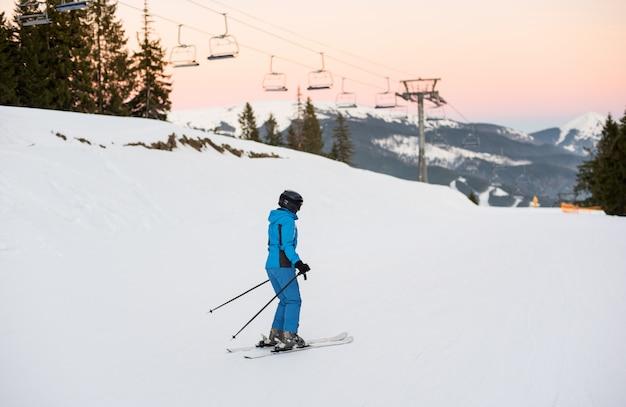 Weiblicher skifahrer auf mitte der skisteigung gegen skilifte
