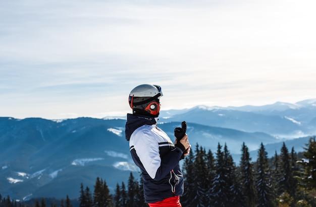 Weiblicher skifahrer, der auf einen hügel genießt schöne landschaft steht