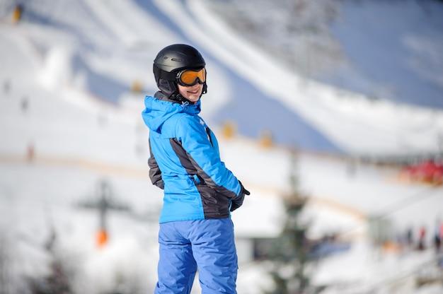 Weiblicher skifahrer, der auf einer skisteigung an einem sonnigen tag steht