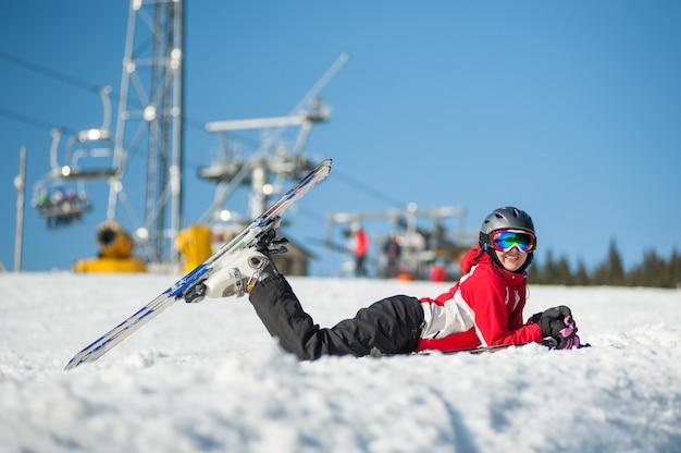 Weiblicher skifahrer, der mit skis auf schneebedecktem an der gebirgsspitze liegt