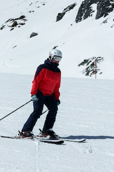 Weiblicher skifahrer in der abschüssigen steigung. wintersport freizeitbeschäftigung