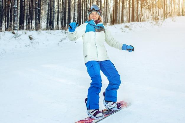 Weiblicher snowboarder, der hinunter den berg snowboarden