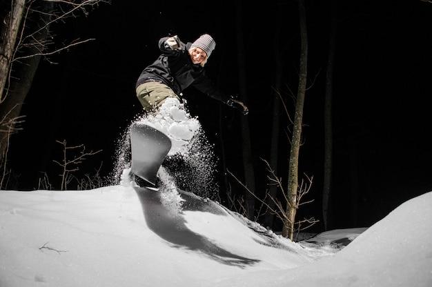Weiblicher snowboarder, der hinunter den berghang nachts reitet
