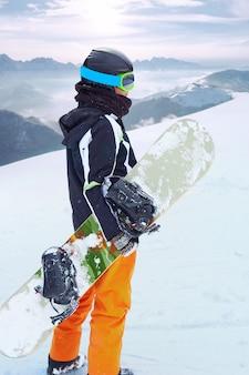 Weiblicher snowboarder, der mit snowboard in einer hand steht und alpine berglandschaft genießt