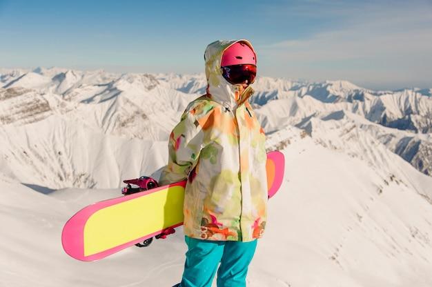 Weiblicher snowboarder in der sportkleidung, die auf der bergspitze steht