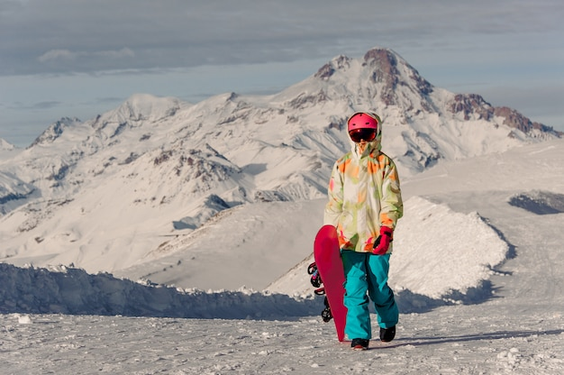 Weiblicher snowboarder in der sportkleidung gehend auf bergspitzen