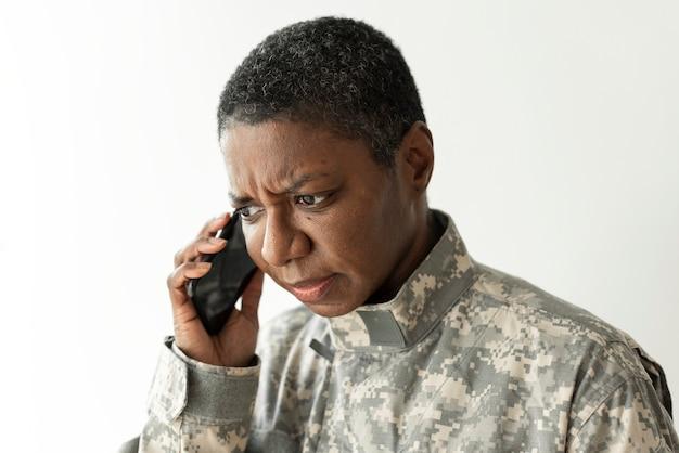 Weiblicher soldat, der auf einer smartphone-kommunikationstechnologie spricht