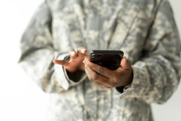 Weiblicher soldat, der auf einer smartphone-kommunikationstechnologie verwendet