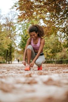 Weiblicher sporteignungsläufer, der zum im park draußen rütteln fertig wird.