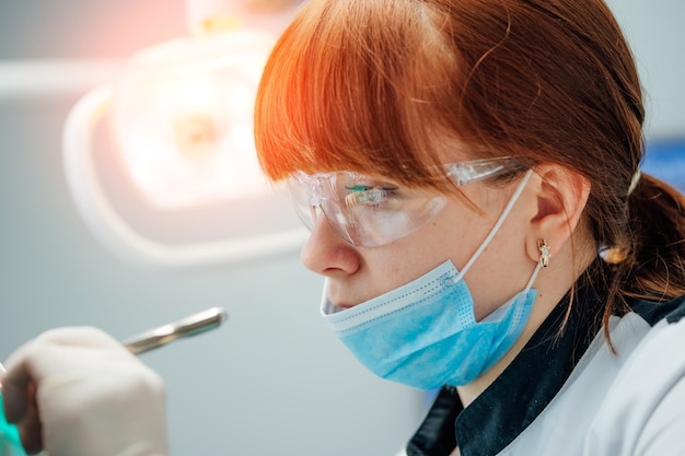 Weiblicher stomatologe in schutzhandschuhen und maske, die die zähne des patienten untersucht. zahnarztkariesbehandlung in der zahnarztpraxis. menschen, medizin, stomatologie und gesundheitskonzept