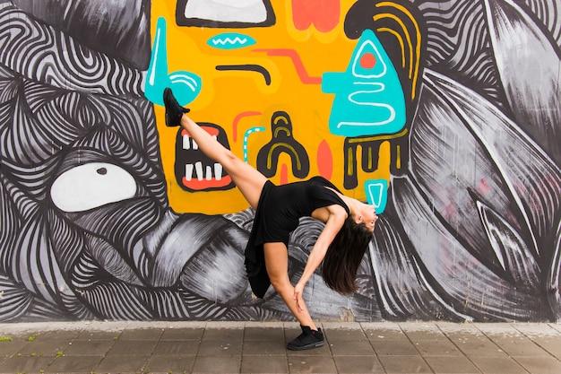 Weiblicher tänzer des tangos, der gegen kreative graffitiwand aufwirft