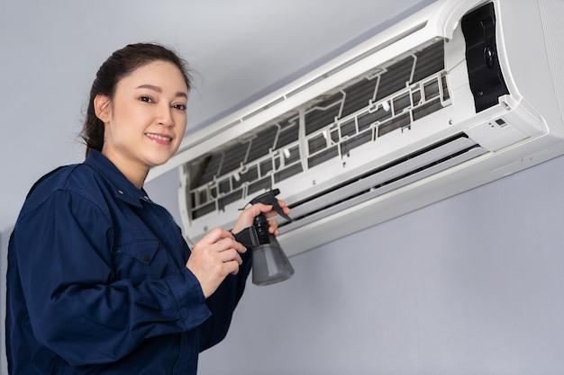 Weiblicher technikerservice, der die klimaanlage im innenbereich reinigt