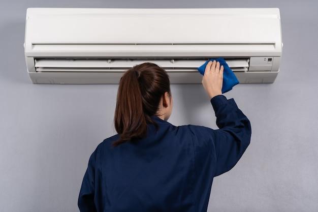 Weiblicher technikerservice, der die klimaanlage mit einem tuch säubert