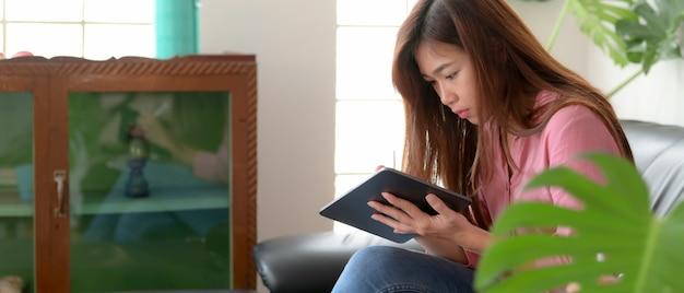 Weiblicher teenager, der digitales tablett beim sitzen auf sofa im wohnzimmer am freien tag verwendet