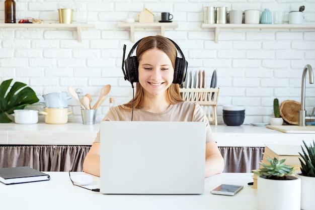 Weiblicher teenager, der kopfhörer trägt, die am laptop zu hause studieren