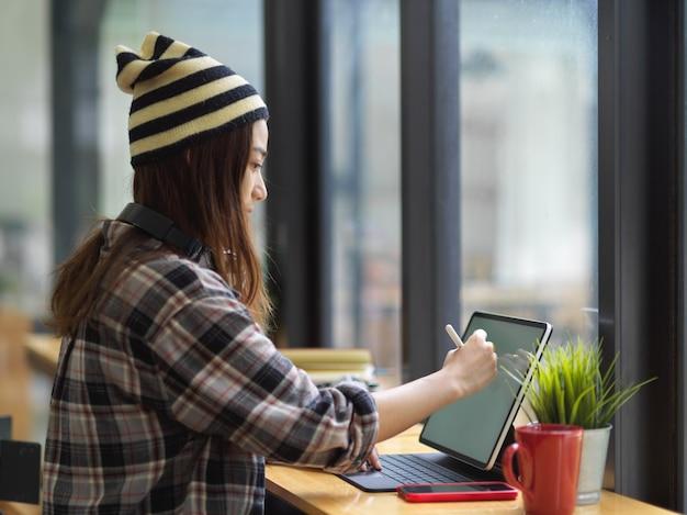 Weiblicher teenager, der modell digitales tablett auf bar im kaffeehaus verwendet